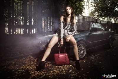 a picture of a woman seating on a parked car